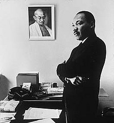 Martin Luther King in front of portrait of Gandhi
